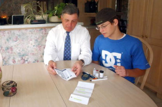 Springfield Mayor Michael Albano and his diabetic son Mikey, 13, sit at the kitchen table with Mikey's supply of Canadian prescription drugs July 29, 2003 in Springfield, Massachusetts.