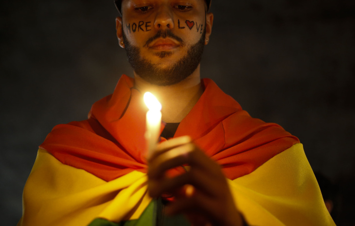 Activists in Sao Paulo, Brazil carry lit candles and flags at a vigil paying tribute to the victims of the Orlando nightclub massacre.