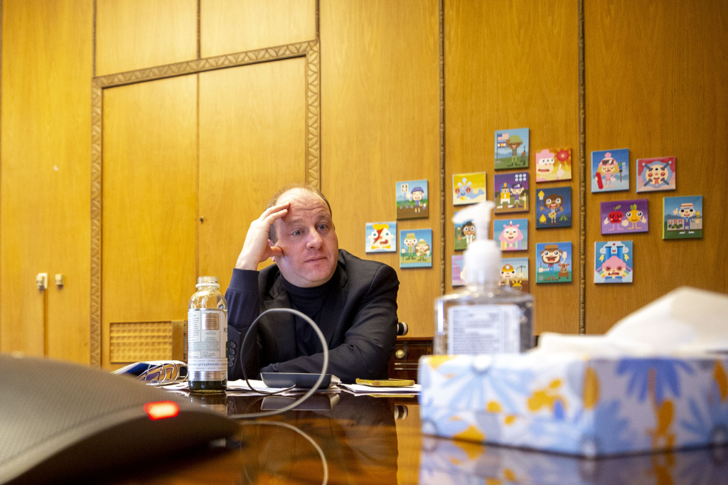 Colorado Gov. Jared Polis listens in to a call with governors around the country, President Trump and Vice President Mike Pence on March 19.