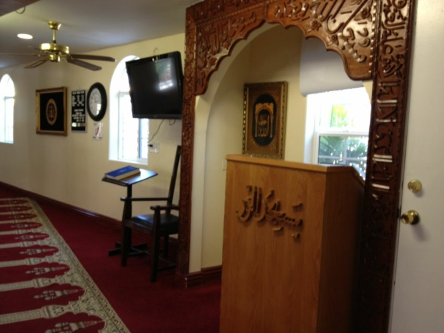 Islamic Center board member Amin Momand shows reporters the little space worshipers have when praying in the small prayer room at the Islamic Center of the South Bay mosque complex.
