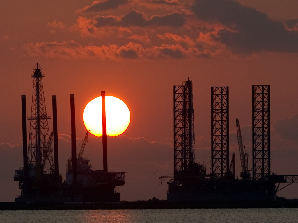 The energy industry was shaken by a trio of events this week that could help shape the future of oil and gas. Here, the sun sets behind two under-construction offshore oil platform rigs in Port Fourchon, La., in 2010.