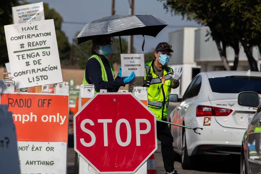 A Testing Center specialists with personal protective equipment (PPE) assist drivers at a drive-in Covid-19 testing site in south Los Angeles, California on November 14, 2020.