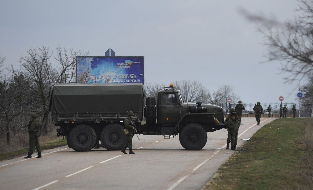 Russian troops block the road way towards the military airport at the Black Sea port of Sevastopol in Crimea, Ukraine, Friday, Feb. 28, 2014. Heightened security is evident with Russian military around Sevastopol, the location for Russia military bases, military airport and Naval Base, while unidentified armed men wearing uniforms without insignia were patrolling another airport serving the regional capital, Ukraine's new Interior Minister Arsen Avakov said on Friday.