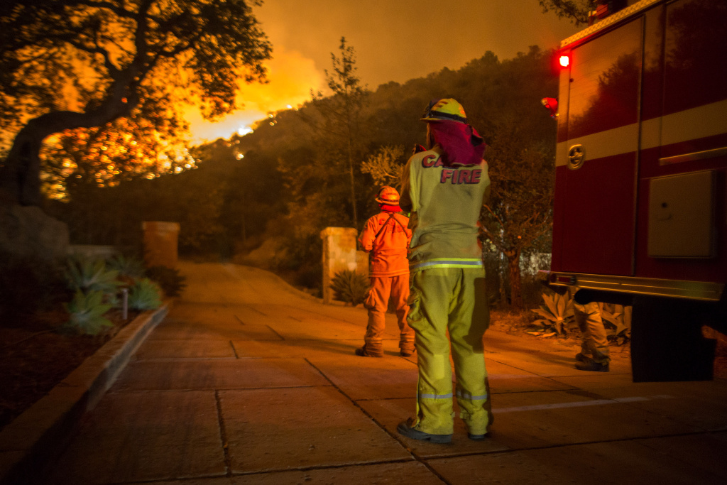 Firefighters watch as the Thomas Fire approaches homes on December 12, 2017 in Montecito, California.