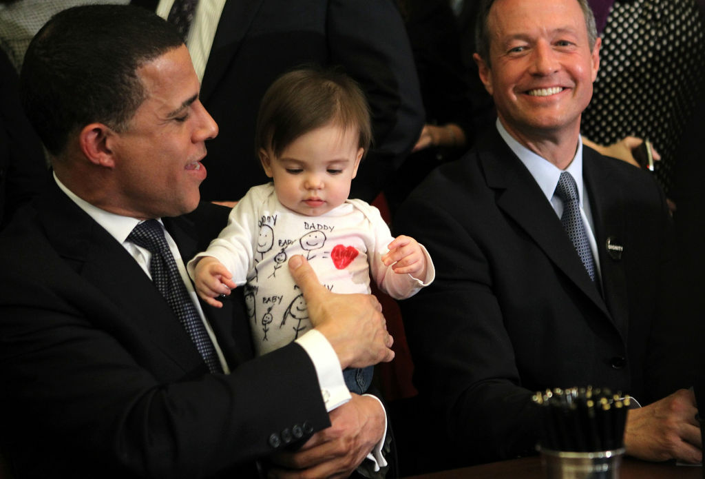 Maryland Lt. Gov. Anthony Brown (L) holds ten-month-old Natalie Vincent (2nd L), daughter of House Speaker Michael Busch's senior policy adviser Jaclyn Vincent, as Gov. Martin O'Malley (R) looks on after he signed the state's recently passed same-sex marriage bill into law during a ceremony at the Maryland State House March 1, 2012 in Annapolis, Maryland. The law is expected to face a referendum in the November election before it goes into effect in January, 2013.