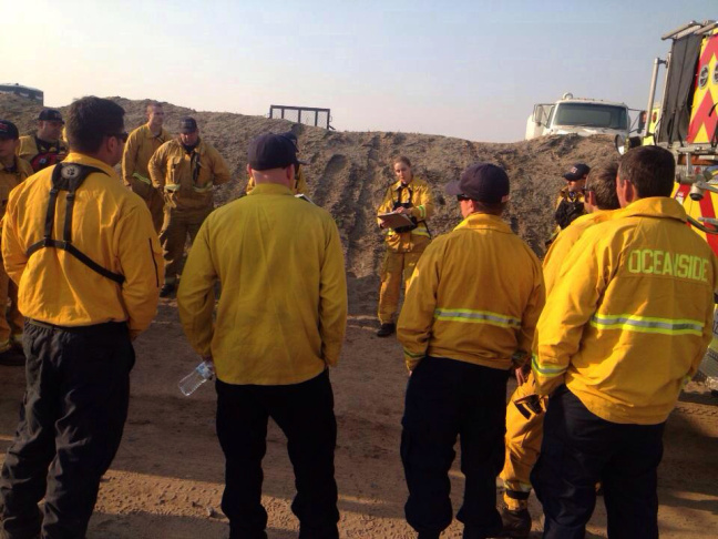 A battalion chief briefs San Diego firefighters deployed to help with the Highway Fire burning in Riverside County.