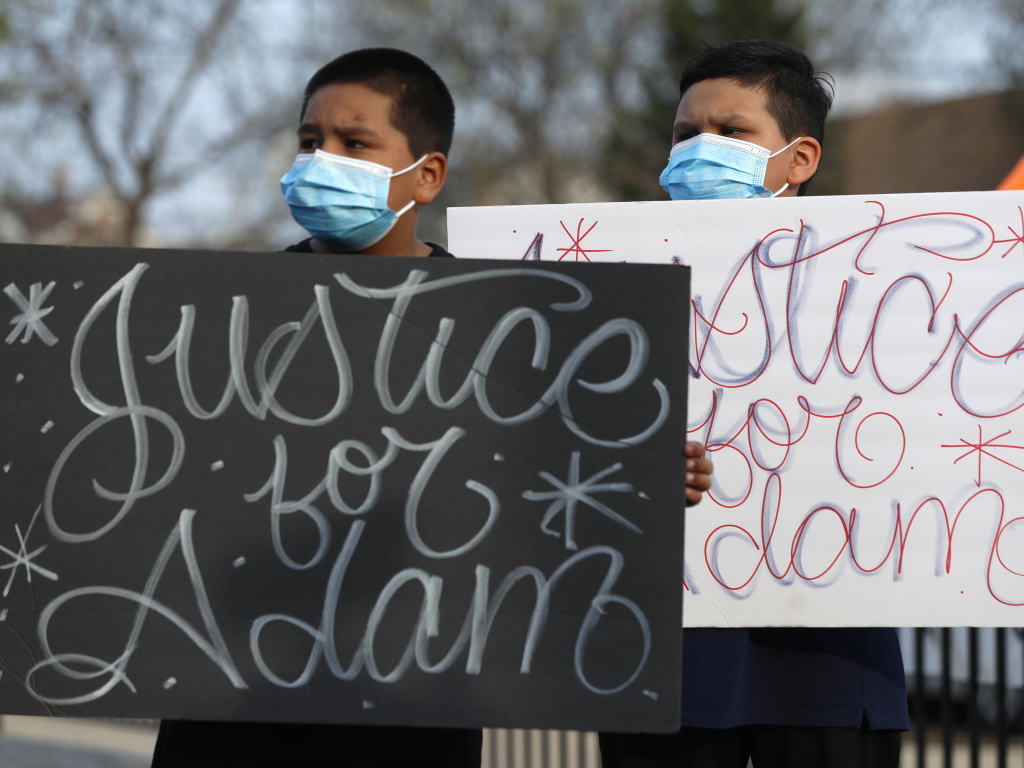Two boys hold signs at an April 6 news conference, days after a Chicago police officer fatally shot 13-year-old Adam Toledo.