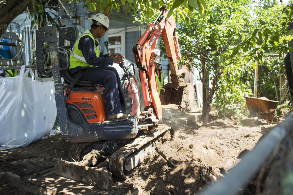A worker removes soil from an East Los Angeles home in April 2016 during an Exide cleanup operation.