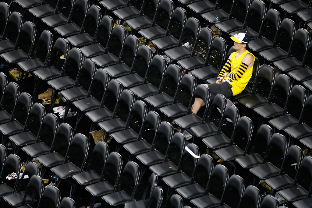 A lone fan of the Michigan Wolverines sits dejected in the stands after Michigan lost 82-76 against the Louisville Cardinals during the 2013 NCAA Men's Final Four Championship at the Georgia Dome on April 8, 2013 in Atlanta, Georgia.