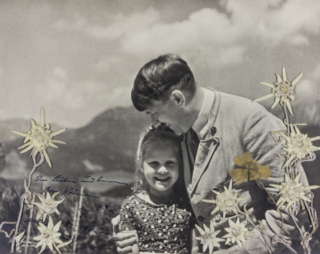In this 1933 photo released by Alexander Historical Auctions, Adolf Hitler embraces Rosa Bernile Nienau at his mountainside Bavarian retreat in Germany. The photograph is inscribed by Hitler himself in dark blue ink.