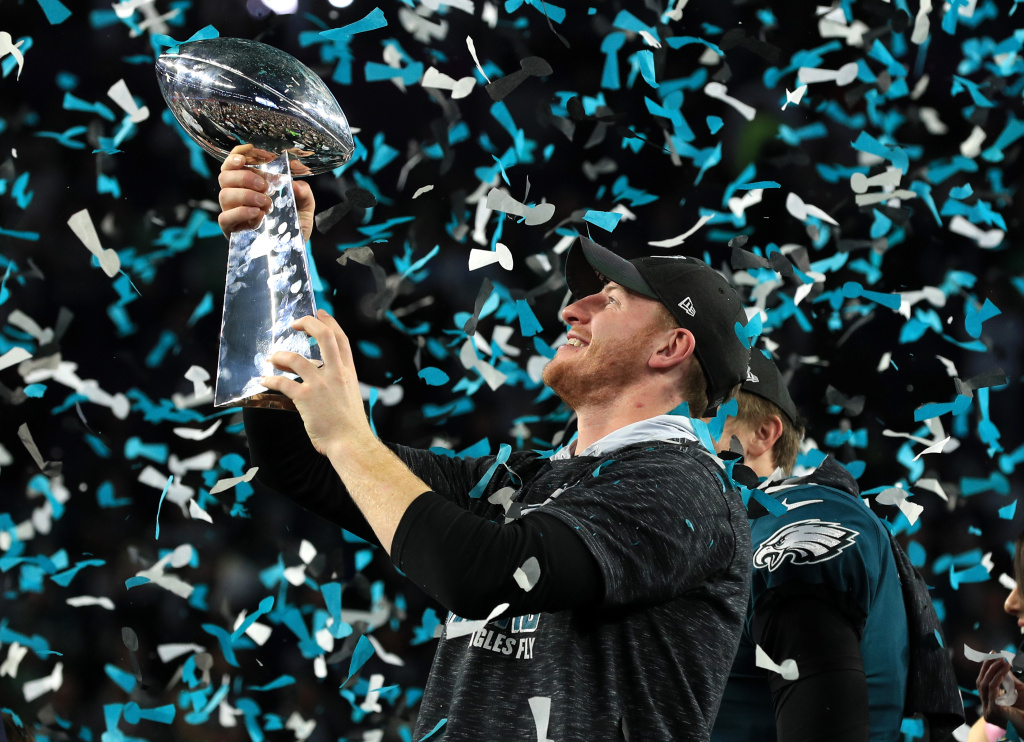 Injured quarterback Carson Wentz #11 of the Philadelphia Eagles holds the Lombardi Trophy after defeating the New England Patriots 41-33 in Super Bowl LII at U.S. Bank Stadium on February 4, 2018 in Minneapolis, Minnesota.