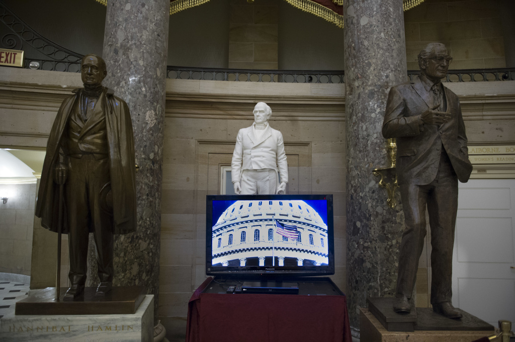 A video monitor sits in front of the statues of, from left, former Vice President Hannibal Hannibal of Maine, former Representative and Senator Daniel Webster and former Arizona Sen. Barry Goldwater in Statuary Hall on Capitol Hill in Washington, Tuesday, Jan. 3, 2017 as the 115th Congress begins. (AP Photo/Cliff Owen)