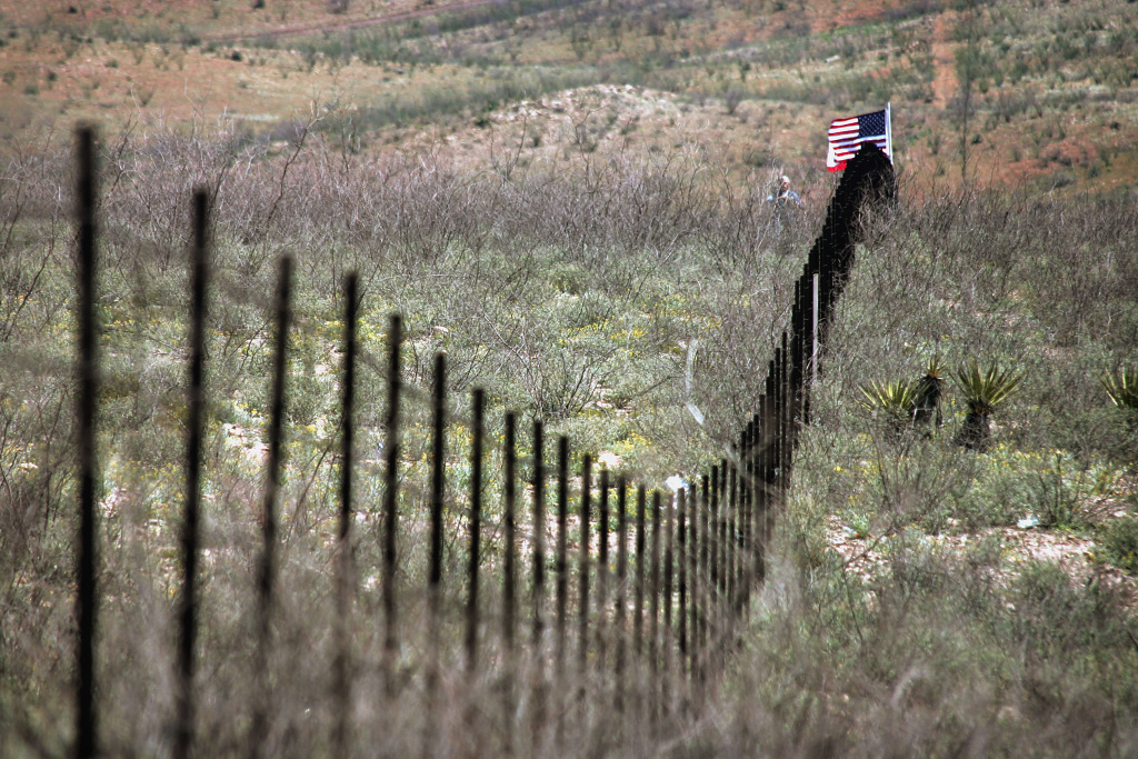 A volunteer from the Minuteman Project stands near an American flag placed in the barbed wire fence which divides the U.S./Mexican border April 4, 2005 near Noco, Sonora Mexico. More than a thousand volunteers from the Minuteman Project are expected to fan out across a 23 mile stretch of the Arizona border to search for Illegal aliens who are making the trek into the United States from Mexico during April.
