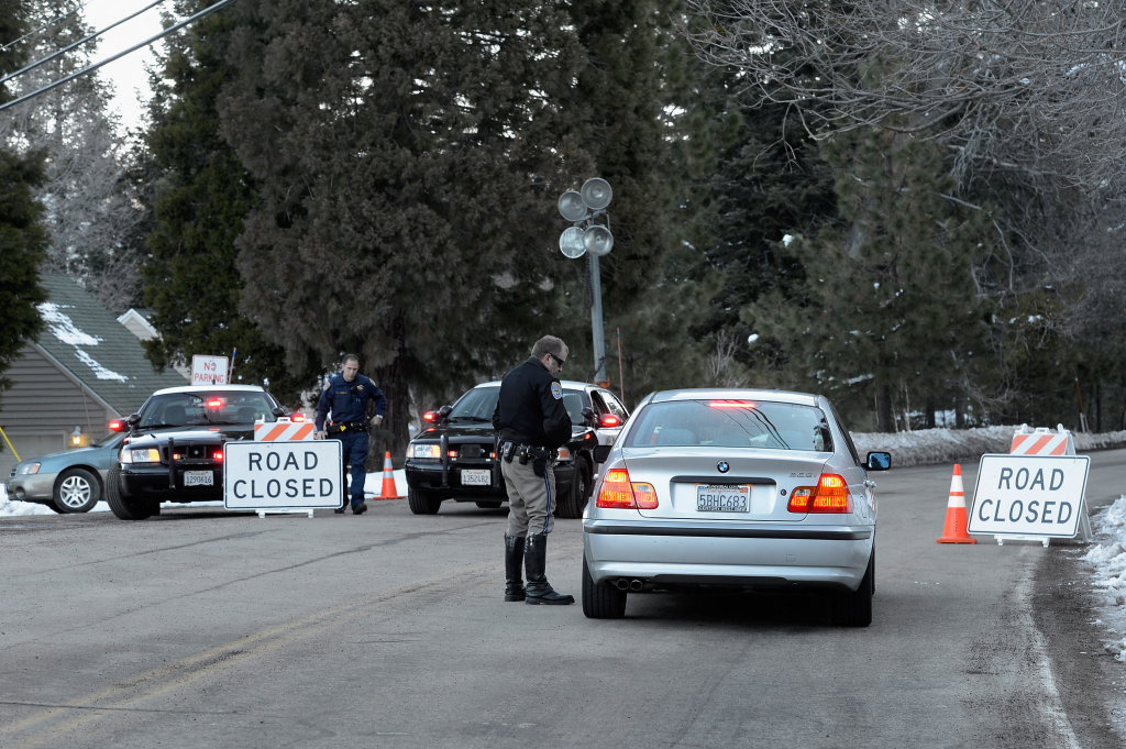 California Highway patrol officers stop a car at a road block a day after a standoff between law enforcement officers and who is believed to be suspected murderer and former Los Angeles Police Department officer Christopher Dorner on February 13, 2013 in Angelus Oaks, California.