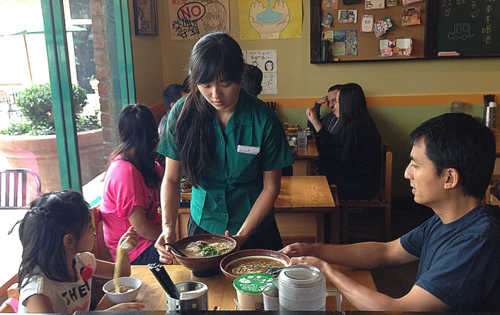 A server dressed as a Taiwanese schoolgirl serves noodles to patrons at Class 302, a popular eatery in Irvine.