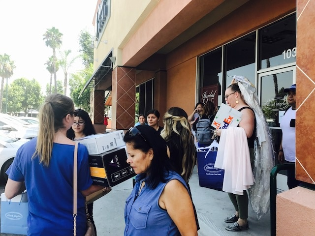 Alfred Angelo employees leave the store Friday morning, July 14, 2017, as crowds ask for help finding their bridal gowns.