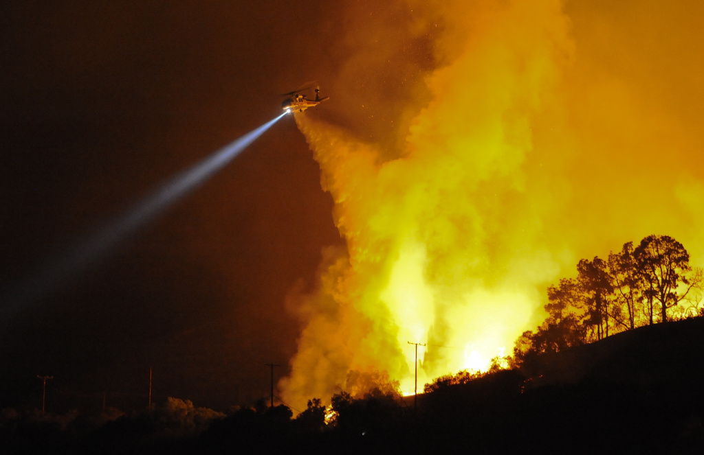 A firefighting helicopter drops water on a fire in Rancho Palos Verdes, Calif., in 2009.