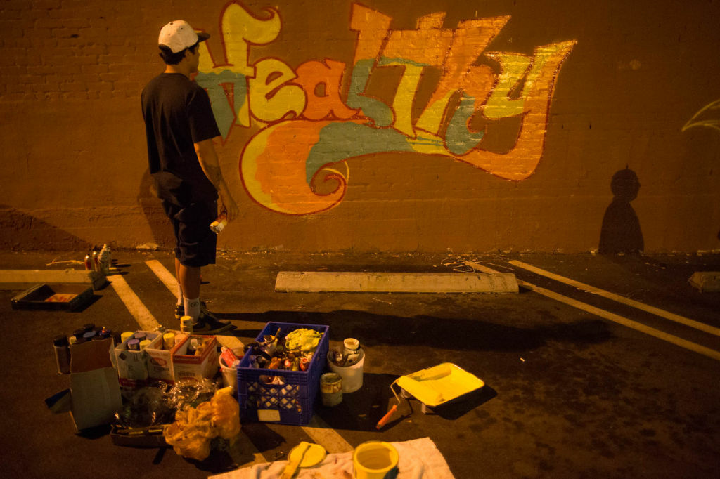 Graffiti Artist Julian, who tags as Naive, takes a break to examine the work he's done on the Triumph Optical mural in Highland Park.