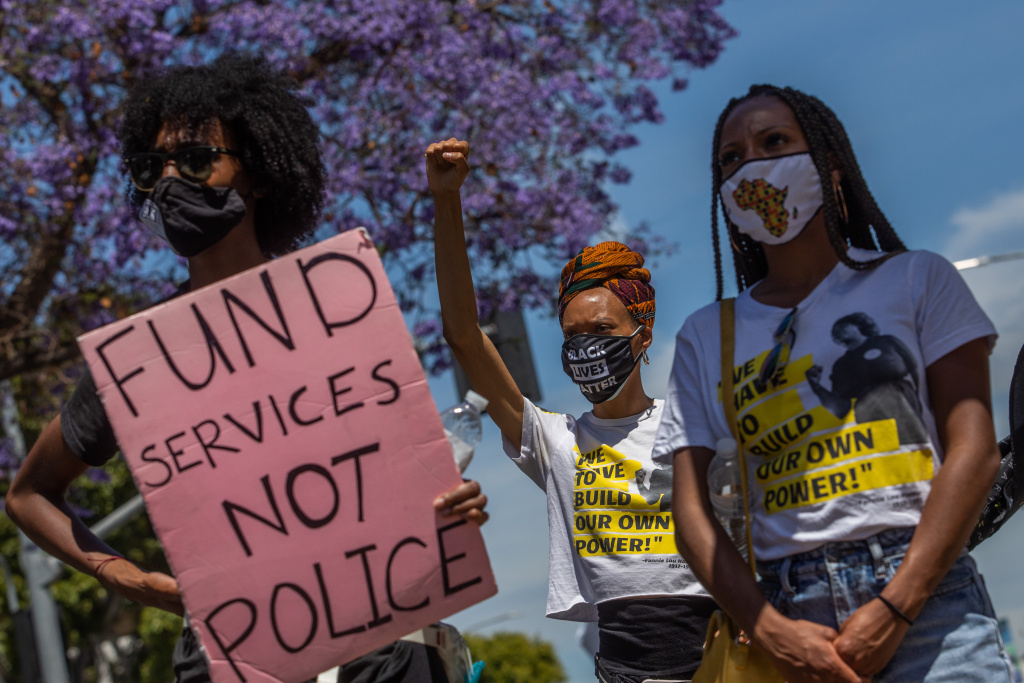 People hold signs during a Black Lives Matter protest near The Los Angeles County Board of Supervisors building on the first anniversary of George Floyd's murder on May 25, 2021 in Los Angeles, California.