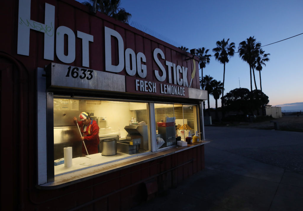 A worker cleans at a carryout hot dog stand on Santa Monica beach on March 17, 2020 in Santa Monica, California.