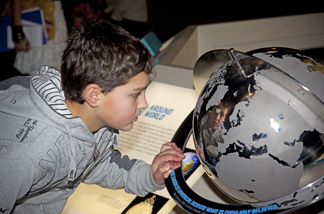"""A child studies a globe at the ""1001 Inventions"" exhibit on Muslim scientific contributions throughout history. The traveling exhibit runs at the California Science Center through December."
