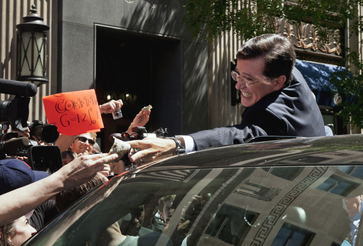 Stephen Colbert grabs cash money from a supporter as he climbs into a vehicle to depart the Federal Election Commission in June, 2011, after the FEC granted his request to form a Political Action Committee.