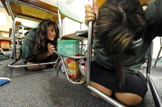 Two girls take cover beneath desks during The Great California ShakeOut, an annual earthquake drill, on Oct. 21, 2010 at Providence High School in Burbank.