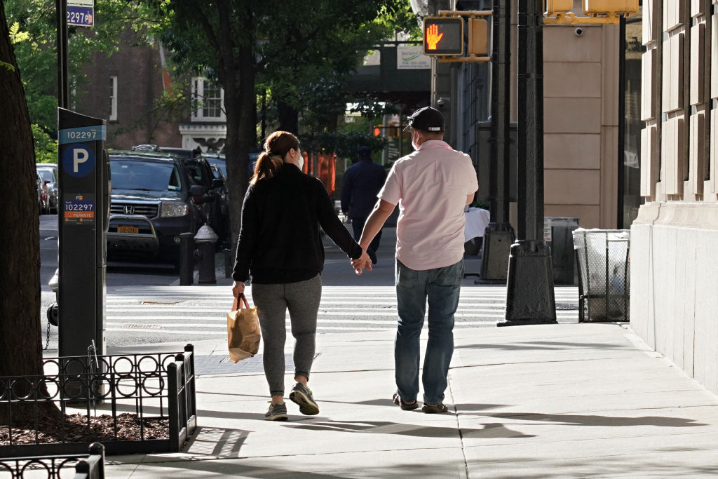 A couple wearing protective masks hold hands during the coronavirus pandemic on May 20, 2020 in New York City.