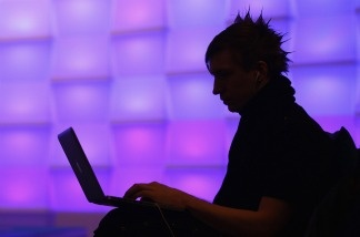 A participant sits with a laptop computer as he attends the annual Chaos Communication Congress of the Chaos Computer Club.