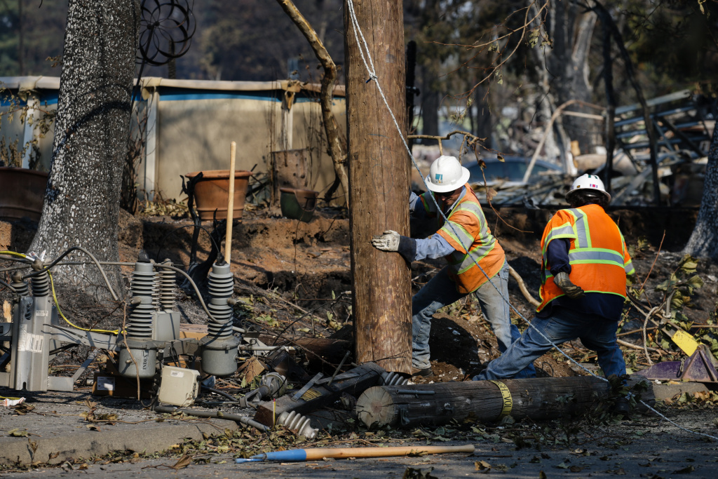 SANTA ROSA, CA - OCTOBER 13: PG&E workers work to repair power lines in the Coffey Park neighborhood following the damage caused by the Tubbs Fire on October 13, 2017 in Santa Rosa, California. Twenty four people have died in wildfires that have burned tens of thousands of acres and destroyed over 3,500 homes and businesses in several Northern California counties.  (Photo by Elijah Nouvelage/Getty Images)