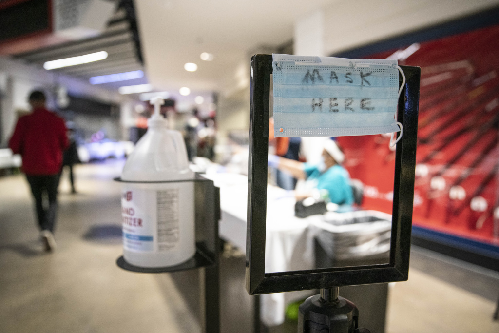 A sign advertising free face masks is seen as people cast their ballots at an early voting center at the Capitol One Arena on October 27, 2020 in Washington, DC.