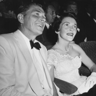 Actor Ronald Reagan and his wife Nancy sitting together holding hands at a party in Hollywood circa 1955.