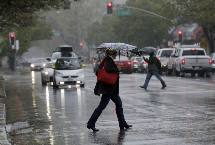 Pedestrians shield themselves from the rain with umbrellas Friday, April 6, 2018, in Santa Rosa, Calif. A fierce Northern California storm Friday shut down Yosemite National Park, threatened mudslides in wildfire-ravaged wine country and could present the first test of a partially repaired offshoot of the nation's tallest dam that nearly collapsed last year.