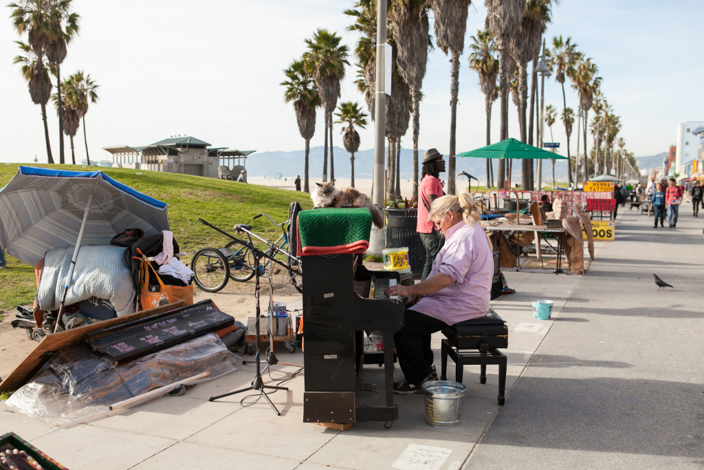 Musician, Nathan Pino and his cat Baby Girl play for tips on the Venice boardwalk.