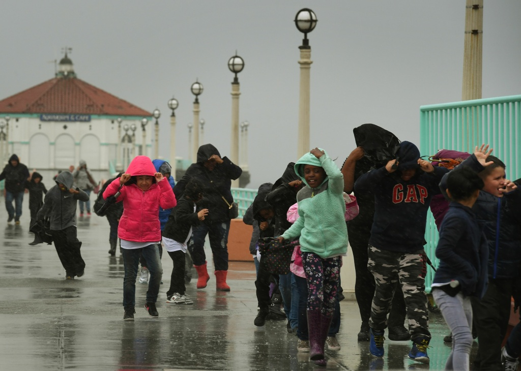 File: Schoolchildren race back to their bus after getting caught in heavy rain during a school excursion, as the strongest storm in six years slams Los Angeles on Feb. 17, 2017. More thunderstorms are forecast this week.