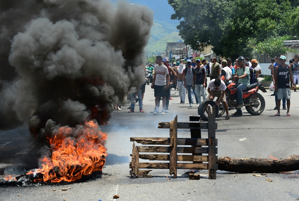 Anti-government activists stand near a barricade burning in flames in Venezuela's third city, Valencia, on August 6, 2017, a day after a new assembly with supreme powers and loyal to President Nicolas Maduro started functioning in the country.
