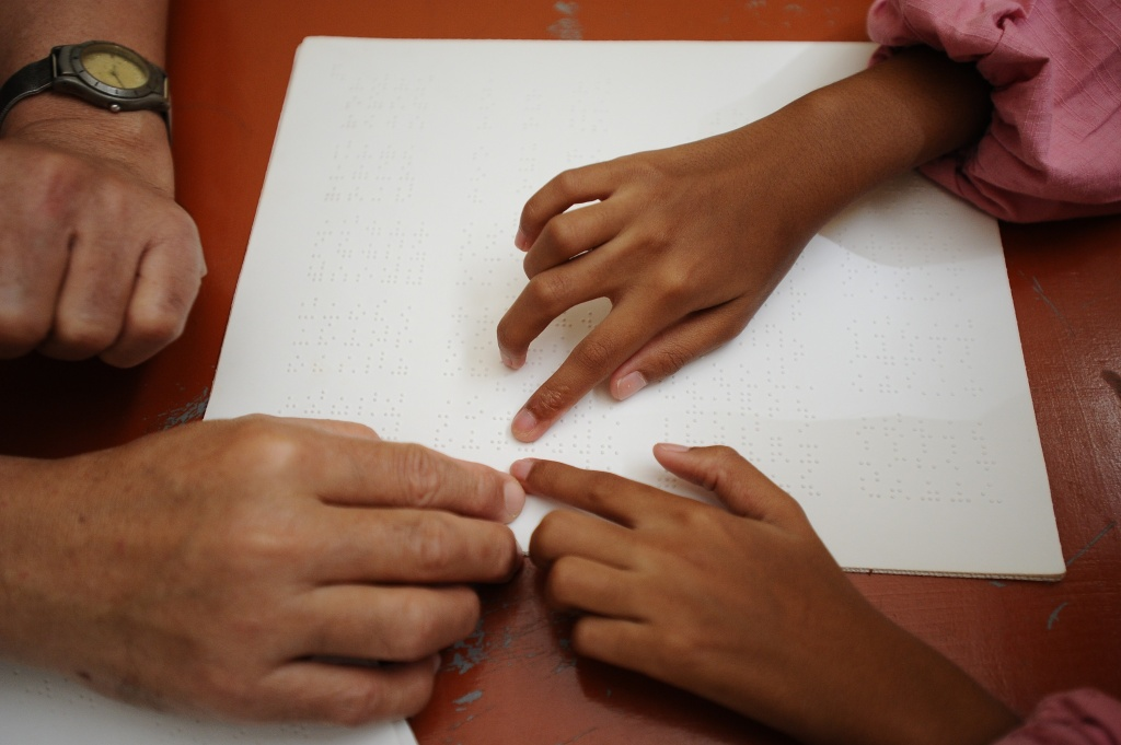 A teacher teaches to a visually impaired students as she reads Braille.