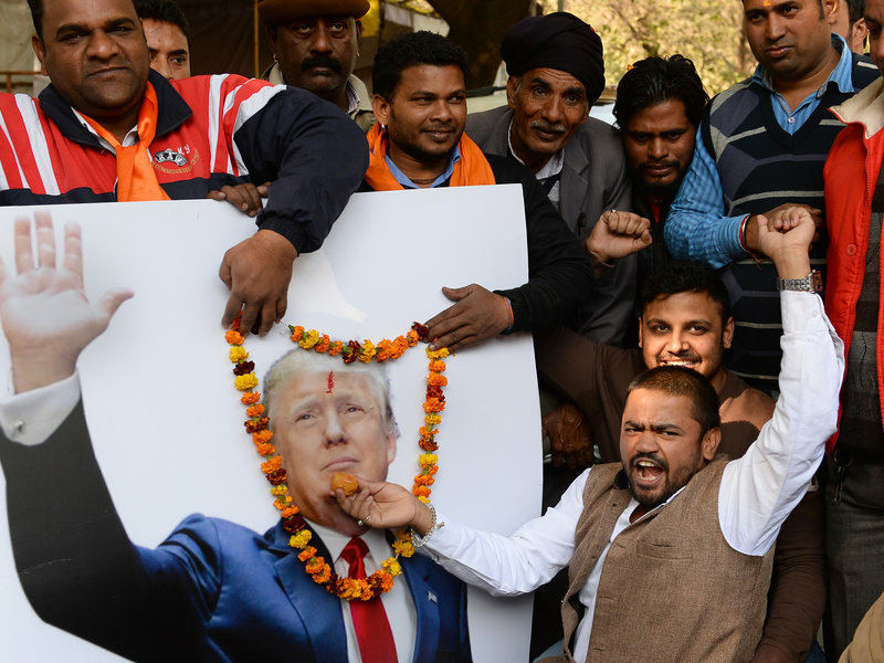 Vishnu Gupta (right), head of India's Hindu Sena group, offers sweets to a garlanded poster of Trump in New Delhi on Thursday.