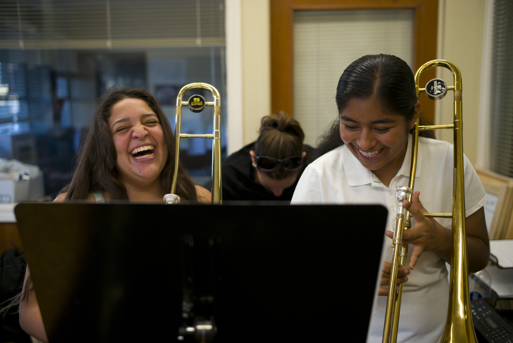 File: Karina Reyes, left, and Damaris Marquez, right, share a laugh during a lesson offered by Harmony Project, a Los Angeles-based nonprofit that provides free music lessons to low-income students and among 14