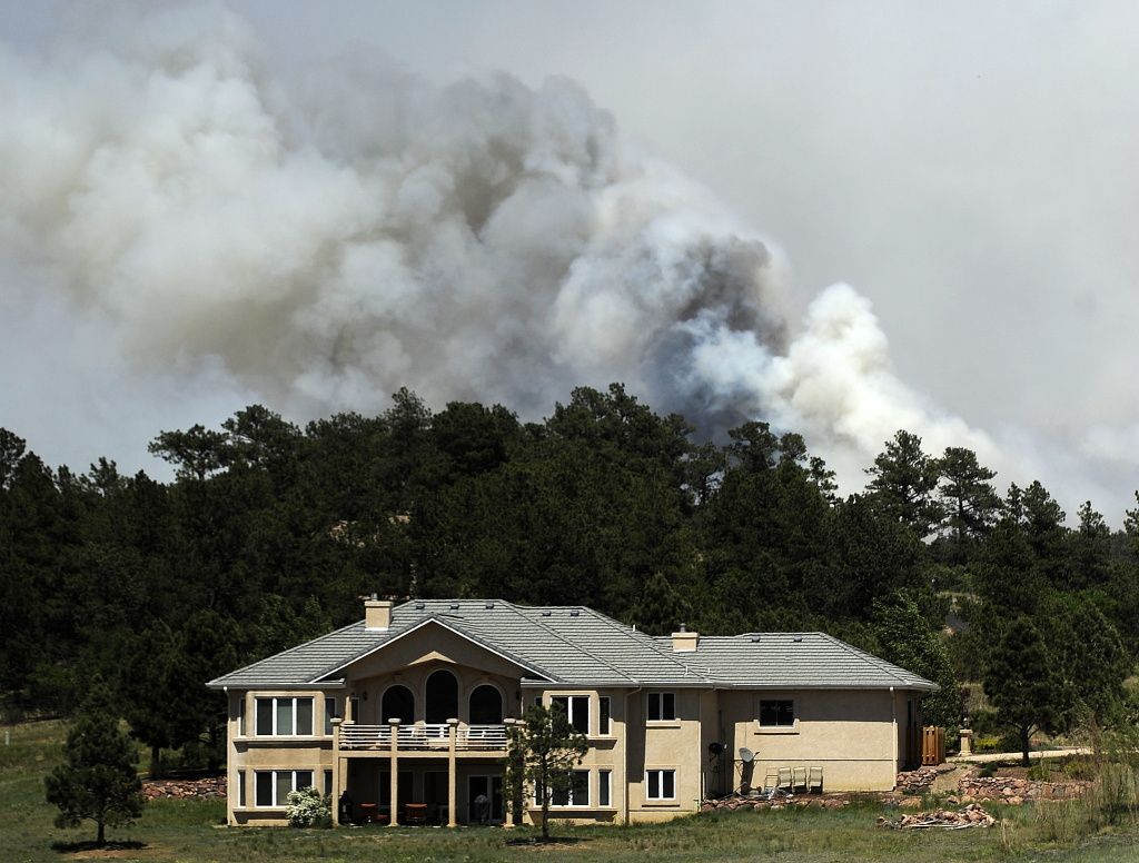 Firefighters in Colorado are hoping rain helps their efforts Monday as they work to contain the most destructive fire in state history. The Black Forest Fire has destroyed 500 homes. (Photo: Smoke billows near a home from the Black Forest Fire on June 12, 2013 north of Colorado Springs, Colo.)