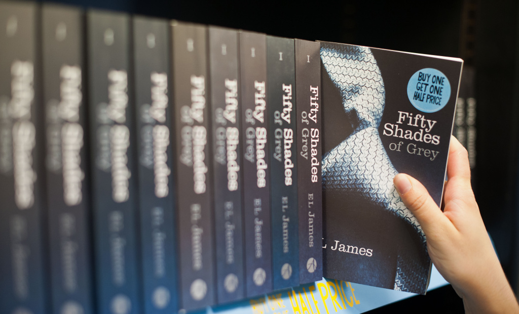 A woman takes a copy of the novel 'Fifty Shades of Grey' from a shelf.