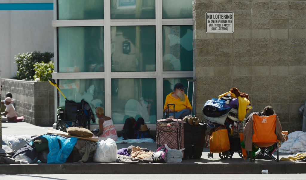 File photo: Homeless people rest on a public sidewalk February 28, 2013 in downtown's Skid Row area of Los Angeles, California. A Valley area hospital accused of dumping patients on Skid Row has agreed to pay $500,000 for homeless services in a settlement with the city.