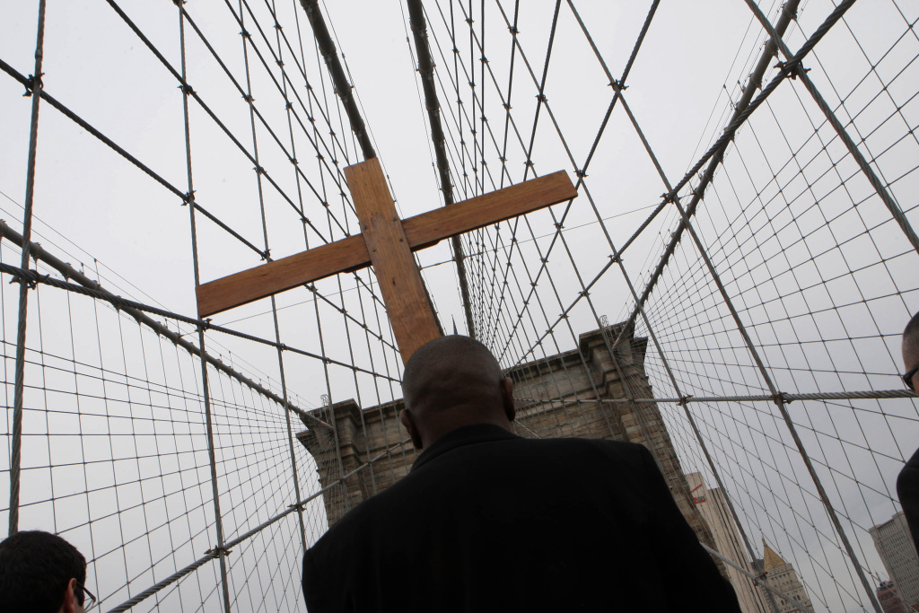 Frank Simmonds carries the cross in the Way of the Cross procession over the Brooklyn Bridge April 22, 2011 in New York City.