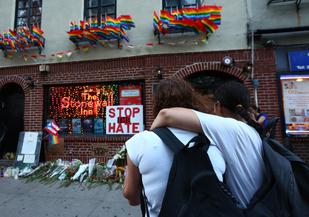 Women embrace before  a make-shift memorial in front of the Stonewall Inn where a vigil was held following the massacre that occurred at a gay Orlando nightclub on June 12, 2016 in New York City. A gunman who allegedly pledged allegiance with ISIS opened fired in the gay nightclub in Florida killing over 50 people.