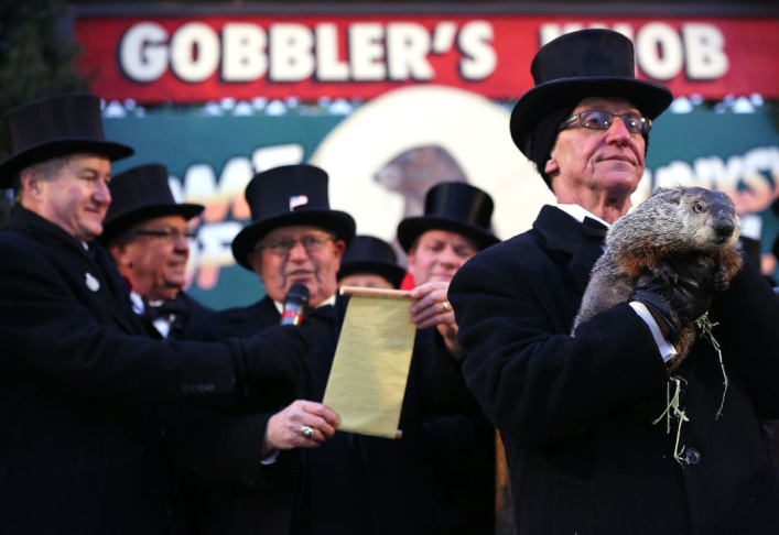 Groundhog co-handler John Griffiths (R) holds up Punxsutawney Phil as co-handler Ron Ploucha (3rd L) looks on after Phil didn't see his shadow and predicting an early spring during the 127th Groundhog Day Celebration at Gobbler's Knob on February 2, 2013 in Punxsutawney, Pennsylvania. The Punxsutawney 'Inner Circle' claimed that there were about 35,000 people gathered at the event to watch Phil's annual forecast.