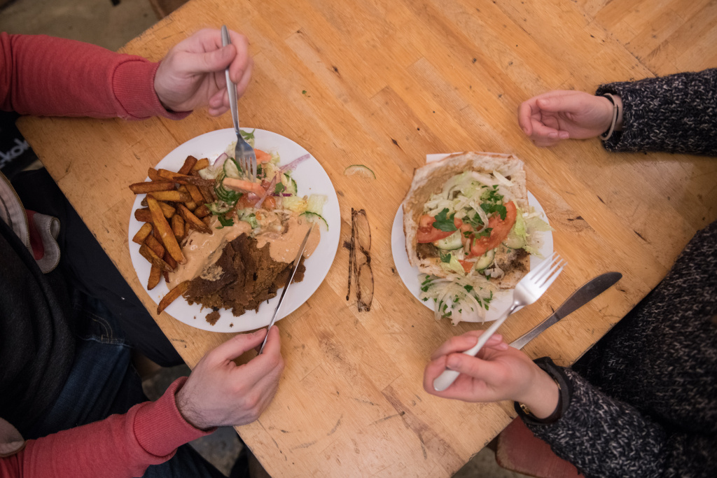 Guests eat a vegan doner plate and a doner kebab at vegan bistro Voener on January 25, 2018 in Berlin, Germany.