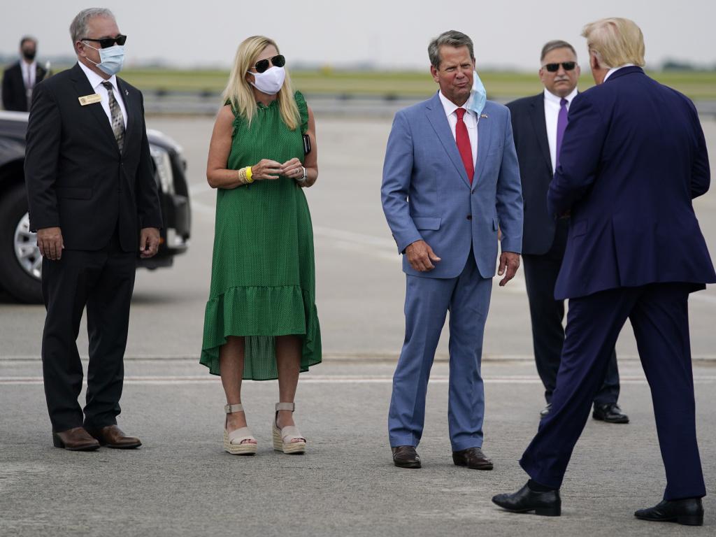 Georgia Gov. Brian Kemp, third from left, greets President Trump at Hartsfield-Jackson Atlanta International Airport, on Wednesday.
