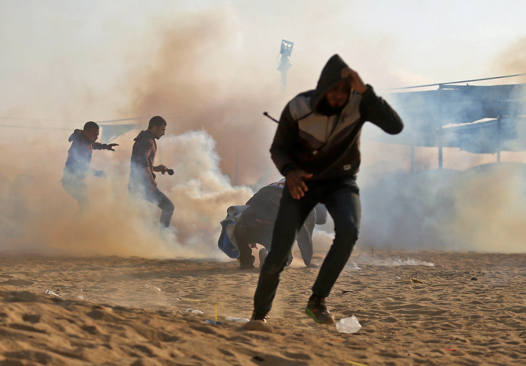 Palestinian protesters flee from tear gas during demonstrations near the border with Israel east of Jabalia in the central Gaza Strip on May 15, 2018 marking 70th anniversary of Nakba -- also known as Day of the Catastrophe in 1948 -- and against the US' relocation of its embassy from Tel Aviv to Jerusalem.