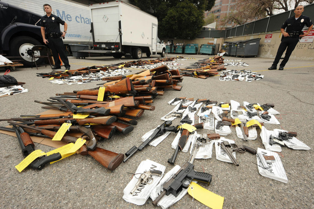 Police guard some of the more than 1,600 firearms which were voluntarily surrendered to police custody over a five-hour period last Saturday are on display at a press conference at police headquarters in Los Angeles, California on May 11, 2009.