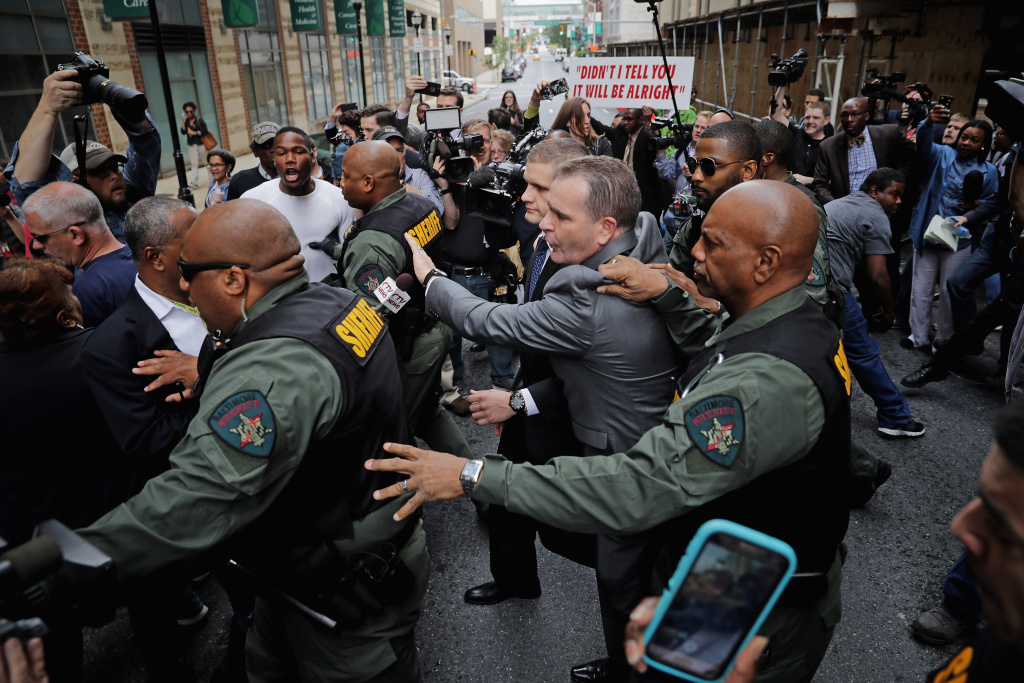 Baltimore City Sheriff's Deputies surround and protect Baltimore Police Officer Edward Nero's family members as demonstrators and members of the news media crowd around the Mitchell Courthouse-West after Nero was found not guilty on all charges against him related to the arrest and death of Freddie Gray in Baltimore, Maryland.